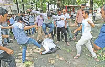 Pro-Awami League Bangladesh Chhatra League activists stomp on and kick a pro-BNP Jatiyatabadi Chhatra Dal activist in front of the Institute of Education and Research in Dhaka University yesterday. JCD activists were waiting to accompany their new central and DU unit leaders to a call on the vice-chancellor when the attack took place